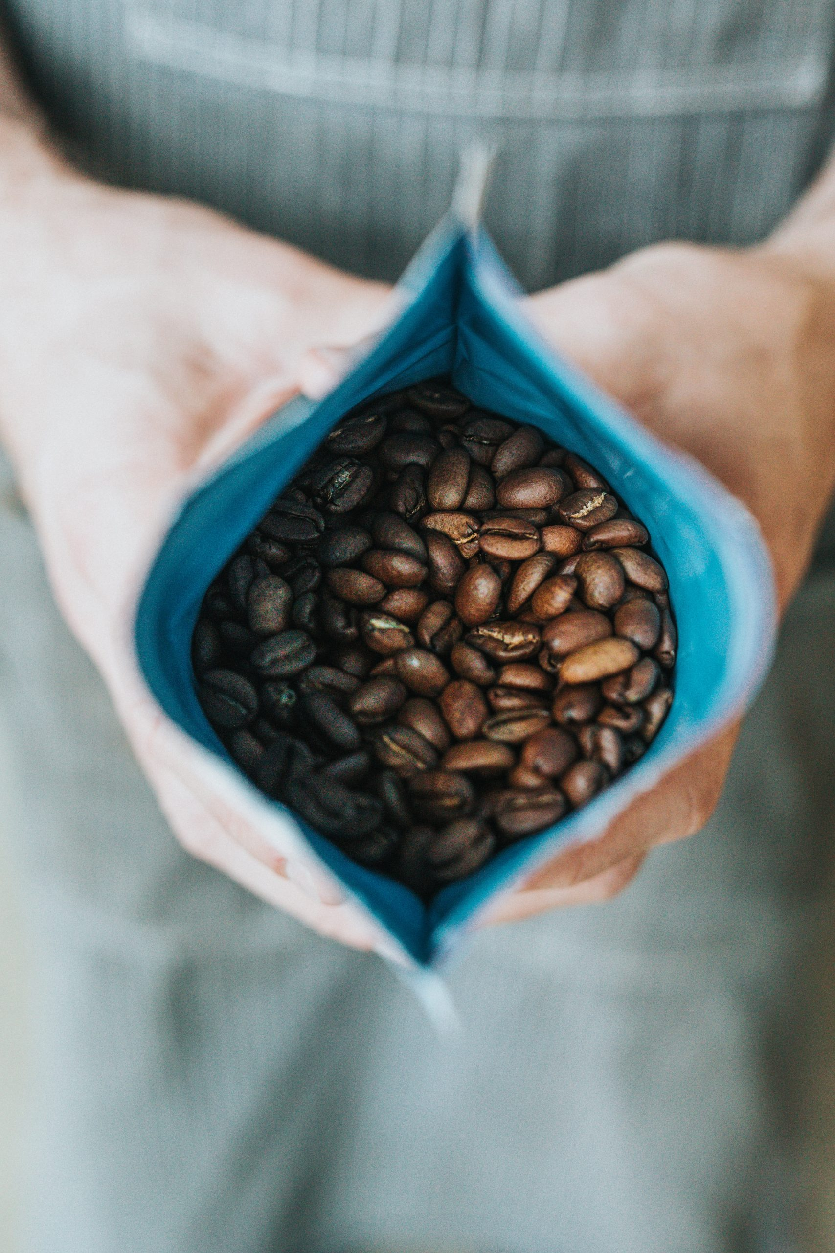 person holding coffee beans in pack